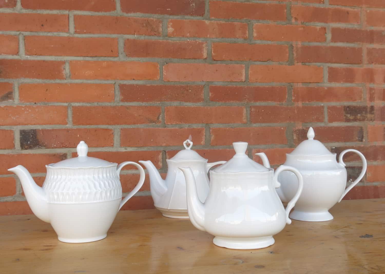 vier verschiedene weiße Porzellanteekannen in unterschiedlichen Stilrichtungen 2