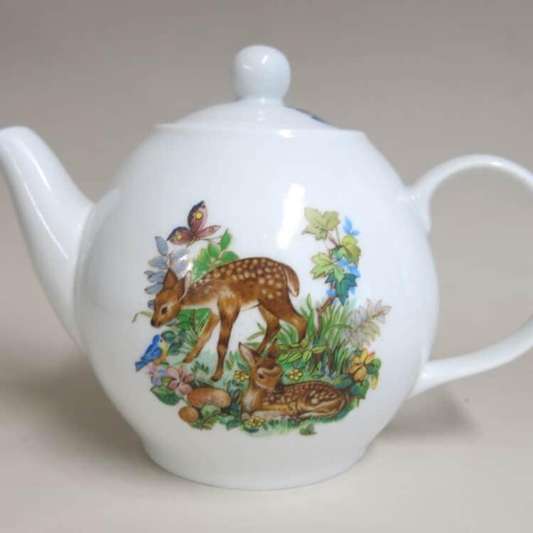 Teekanne aus weißem Porzellan mit Rehitzen im Wald