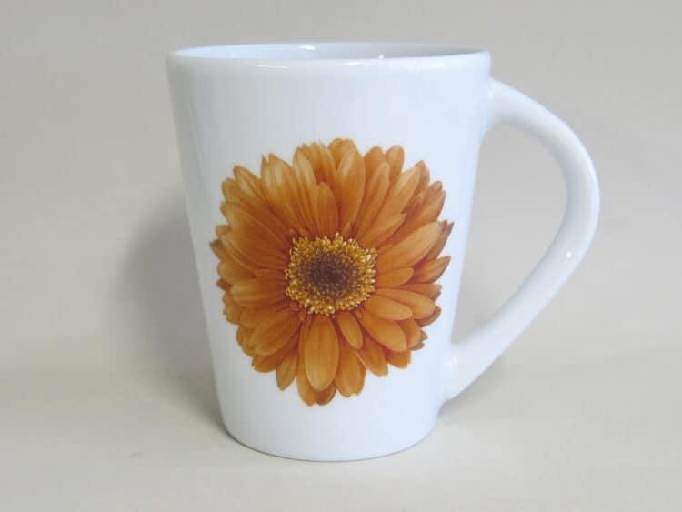 Becher 260 ml mit orangener Gerbera auf weißem Porzellan
