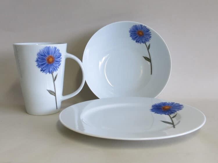 Dreiteiliges Frühstückgsgeschirr aus Porzellan mit Teller 21,5 cm Becher 350 ml und Schüssel 17 cm mit Blume blauer Aster.